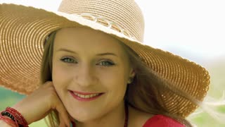Pretty girl in straw hat smiling to the camera while being outdoors
