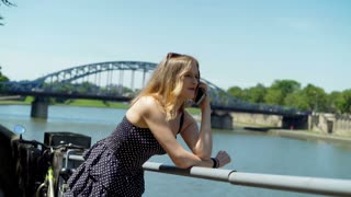 Pretty girl in vintage dress chatting on cellphone next to the river