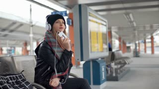 Pretty girl in warm clothes listening music on platform and smiling to the camer