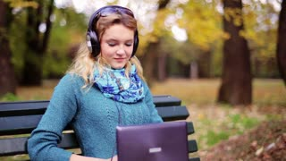 Pretty girl listening music in the park and smiling to the camera