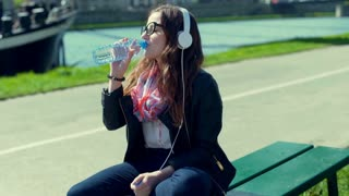 Pretty girl listening music on headphones and drinking water while sitting on th