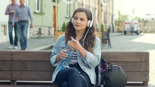 Pretty girl listening music on headphones and drinking water