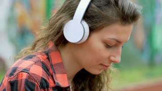 Pretty girl listening music on headphones and looking happy