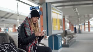 Pretty girl listening music on headphones and texting on smartphone
