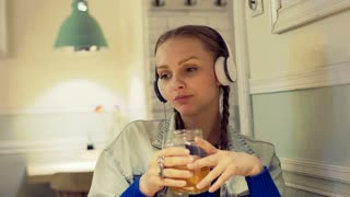 Pretty girl listening music on headphones in the cafe and holding jar of tea