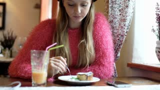 Pretty girl looking happy while sitting in the cafe and eating delicious cake