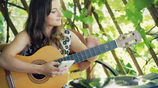Pretty girl looking on smartphone and tunning her guitar in the arbor