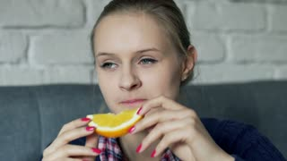 Pretty girl looking thoughtful and eating orange