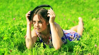 Pretty girl lying on the green meadow and listening music on headphones