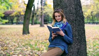 Pretty girl reading book in the park and smiling to the camera