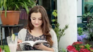 Pretty girl reading interesting book and smiling to the camera