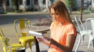 Pretty girl reading menu in the outdoor cafe and smiling to the camera