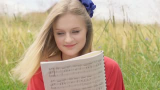 Pretty girl reading notes and smiling to the camera in the grain field
