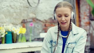 Pretty girl singing while listening music on headphones and smiling to the camer