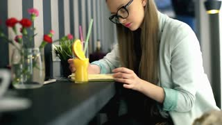 Pretty girl sitting in the cafe and checking her journal, steadycam shot