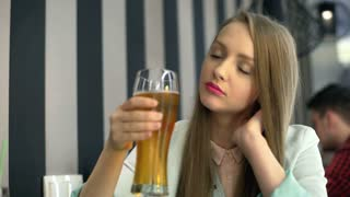 Pretty girl sitting in the cafe and drinking beer