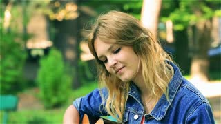 Pretty girl sitting in the park and playing on the guitar, steadycam shot