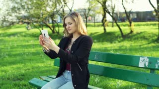 Pretty girl sitting on the bench and doing selfies on smartphone