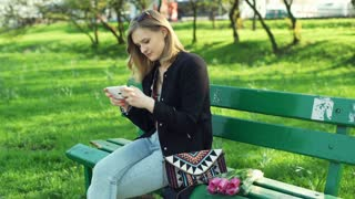 Pretty girl sitting on the bench and texting on smartphone