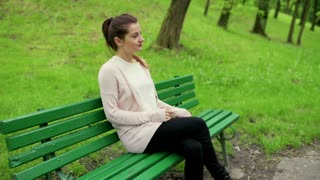 Pretty girl sitting on the bench in park and relaxing