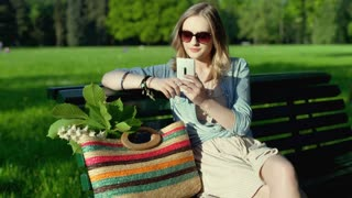 Pretty girl sitting on the bench in the park and texting on smartphone