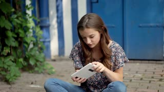 Pretty girl sitting on the ground and playing a game on tablet