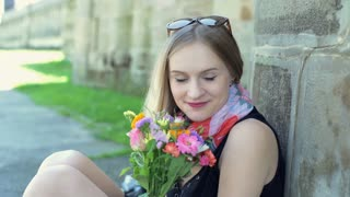 Pretty girl sitting with bunch of colorful flowers and smiling to the camera