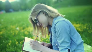 Pretty girl smiling to the camera and writing something in her journal