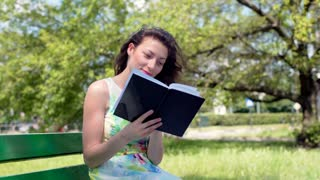 Pretty girl smiling to the camera while reading book in the park