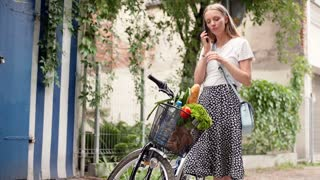 Pretty girl standing with her bicycle and talking on cellphone