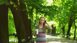 Pretty girl texting on smartphone and drinking coffee in the park