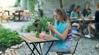 Pretty girl texting on smartphone and smiling to the camera in the cafe