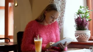 Pretty girl texting sms on smartphone while reading book in the cafe