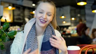 Pretty girl touching her scarf and smiling to the camera, steadycam shot