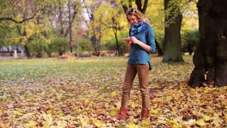 Pretty girl walking in the park at autumn and using smartphone
