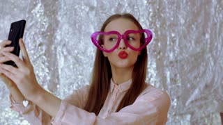 Pretty girl wearing heart glasses and doing selfies on smartphone