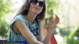 Pretty girl wearing sunglasses and smiling to the camera in the park