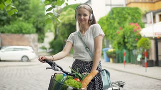 Pretty girl with bicycle listening music on headphones and smiling to the camera