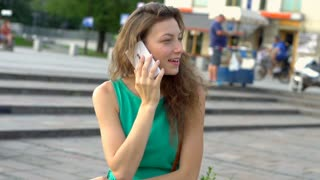 Pretty girl with curly hair chatting on cellphone, steadycam shot, slow motion
