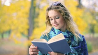 Pretty girl with freckles reading book in the park