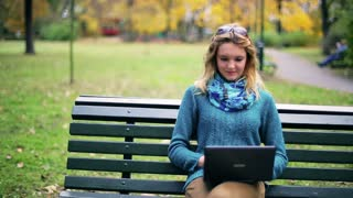 Pretty girl working on laptop and smiling to the camera in the park