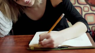 Pretty girl writing in the notebook and smiling to the camera, steadycam shot