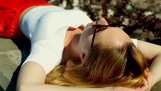 Pretty, skinny girl sleeping outdoors at sunny day and wearing sunglasses