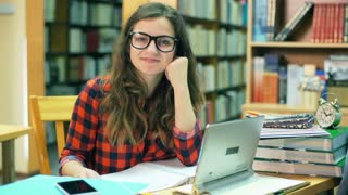Pretty student sitting in the library and smiling to the camera