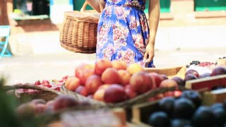 Pretty woman standing on fruit market with basket and smiling to the camera
