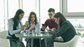 Quiet businesspeople sitting and working on cellphones