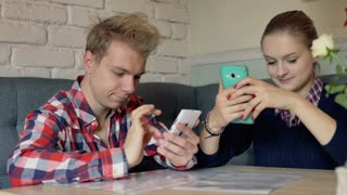 Quiet couple sitting in the cafe and browsing internet on smartphone