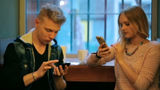 Quiet couple sitting in the cafe and using smartphones