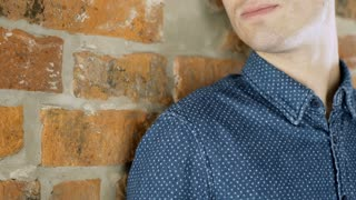 Red haired man standing next to the brick wall and smiling to the camera, steady