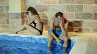 Relationship difficulties: couple after quarrel by the swimming pool at night